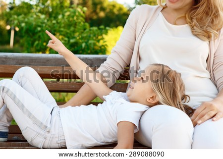 Mommy look. Portrait of little cheerful girl lying on bench near her mother and pointing up. - stock photo