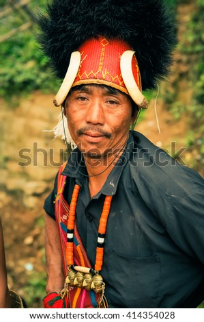 Mon, Nagaland - April 2012: Native man with traditional large hat with fur and bones wears grey shirt at Aoleang festival in Mon, Nagaland. Documentary editorial.