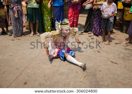 MON STATE, MYANMAR - APRIL 13, 2015: An unidentified Burmese man dances in traditional style for money during Songkran festival (traditional New Year Day) in Mawlamyine, Mon State, Myanmar.