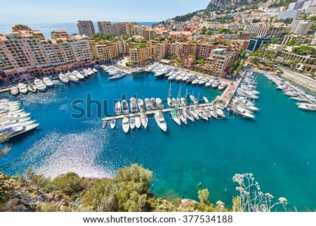 Monaco, Fontvieille, 29.08.2015: Port Fontvieille, panorama, topview from Monaco Ville, azure water, sun reflections in water, harbor, sunny day, luxury apartments, yachts, rocks