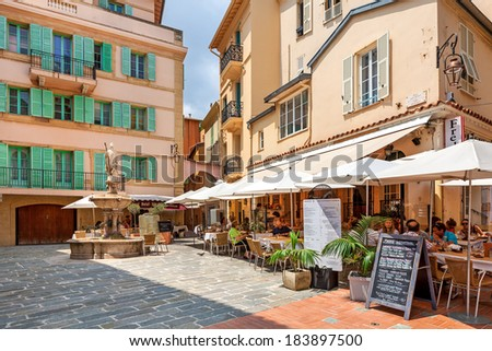 MONACO-VILLE, MONACO - JULY13, 2013: People having dinner in outdoor restaurant on small quiet square surrounded by houses in Monaco-Ville, Monaco  - popular touristic resort and place to visit. - stock photo