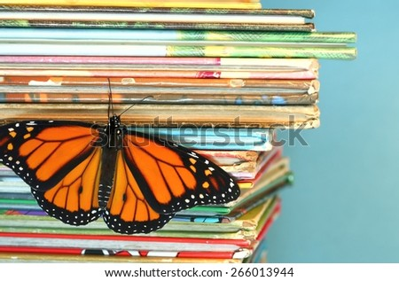 Monarch butterfly with open wings climbing up pile of books - stock photo