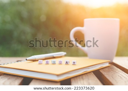Monday written in letter beads and a coffee cup on table - stock photo