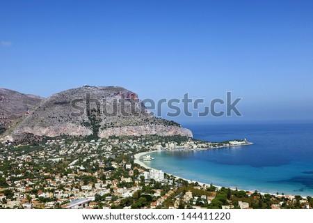 Mondello Beach lies between two cliffs called Monte Gallo and Monte Pellegrino. Mondello, Sicily, Italy. - stock photo