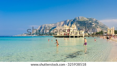 MONDELLO, SICILY, ITALY - MAY 26; people walking and bathing in clear turquoise waters of Mondello beach on May 26, 2011. - stock photo