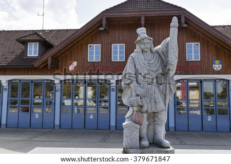 MONDSEE, AUSTRIA - SEPTEMBER 10, 2015: Firefighter statue in front of local fire department. Mondsee is a town in the Austrian state of Upper Austria located on the shore of the lake Mondsee.