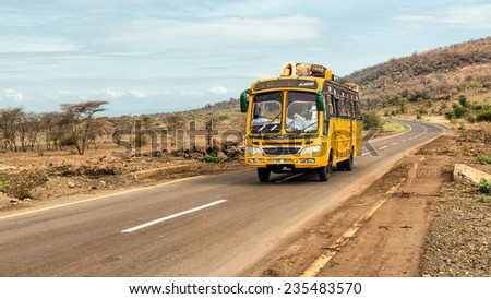 MONDULI, TANZANIA - OCTOBER 21, 2014 : Typical and overcrowded african bus driving from Arusha to Namanga, Tanzania. - stock photo
