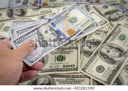 Money: a hand holding money 100 dollar bills on stack of 100 dollar bills. concept of using money in paying with full of money close up of money in hand and money background. US money, US dollars - stock photo
