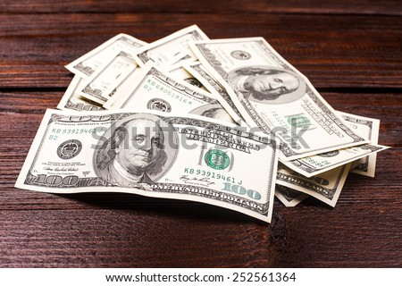 money american hundred dollar bills carelessly scattered on the wooden table - stock photo