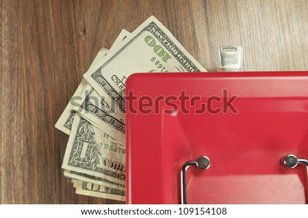money and a box for storage on the wooden table