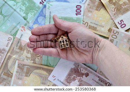 Money and a hand holding a house - stock photo