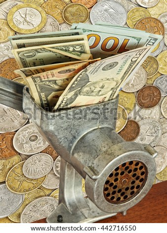 Money and business concept.Dollar banknotes in meat grinder on lot of different coins background. - stock photo