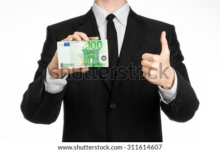 Money and business theme: a man in a black suit holding a bill of 100 euros and shows a hand gesture on an isolated white background in studio