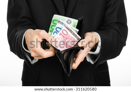 Money and business theme: a man in a black suit holding a purse with paper money Euro isolated on white background in studio