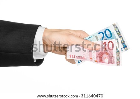 Money and business topic: hand in a black suit holding banknotes 10 and 20 euro on white isolated background in studio