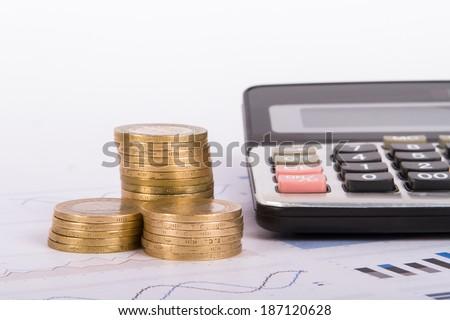 Money and calculator on financial data bar charts. - stock photo