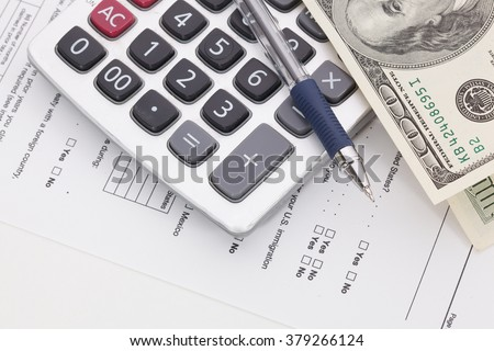 Money and calculator on tax form background - stock photo