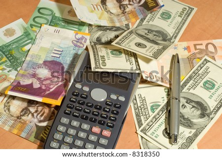 money and calculator on the table - stock photo