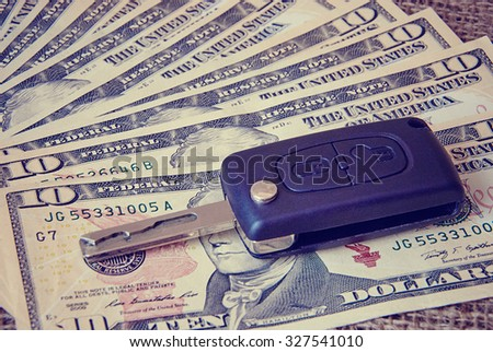 Money and car keys on a burlap background. Toned image - stock photo