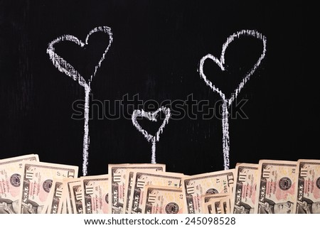 money and chalk-drawn heart on the board - stock photo