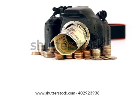 Money and DSLR camera surrounded by stack of coins and U.S. banknote on white background. - stock photo
