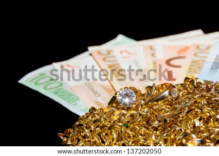 Money and gold jewellery against a black background. - stock photo