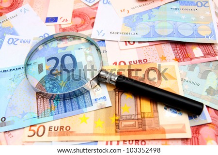 Money and magnifier. - stock photo