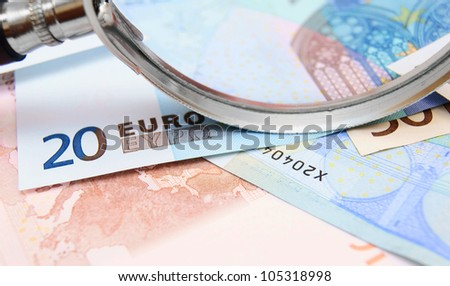 Money and magnifier . . - stock photo