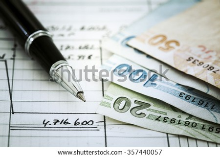 Money and pen on document