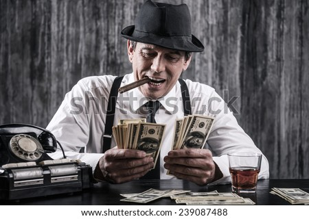 Money and power. Senior gangster in shirt and suspenders counting money and smiling while sitting at the table - stock photo