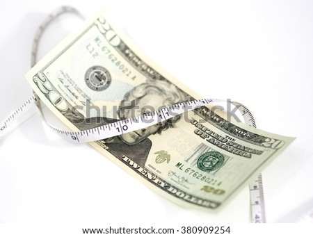 Money and Tape Measure - Measuring wealth - stock photo