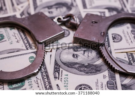 money and the law, handcuffs on money, hundred dollar bills front face side and handcuffs. background of dollars, savings, taxes and law