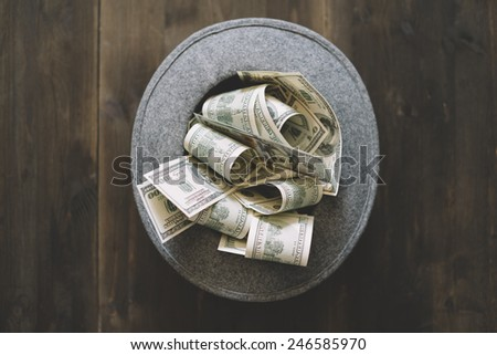 money and the wool hat on the wooden background,selective focus - stock photo