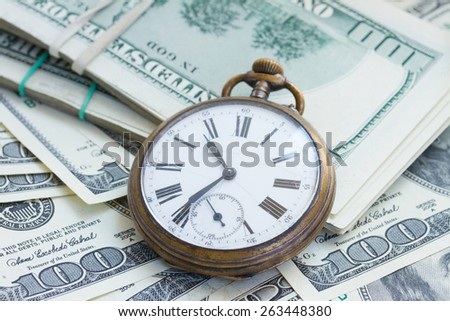 money and time concept - antique  pocket watch on pile of american dollars - stock photo