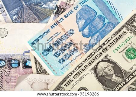 Money background with US dollars, British pounds, Lithuanian litas and Zimbabwe hundred trillion dollars - stock photo