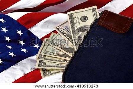 Money bag containing US Currency including a hundred dollar bill, a fifty, two twenties and three ones on an American flag - stock photo