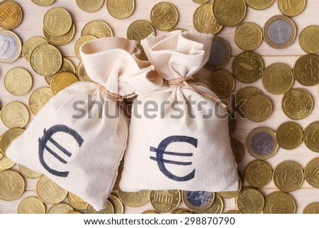 Money bags and euro coins over wooden background, focus on money bags - stock photo