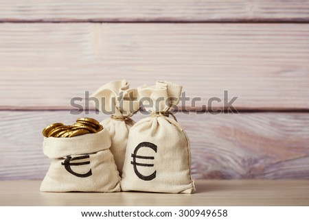 Money bags with euro coins on wooden background - stock photo
