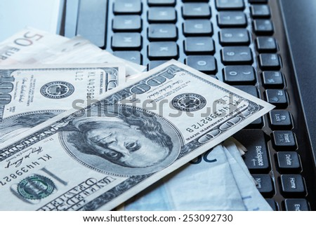 Money banknotes over laptop keyboard - stock photo