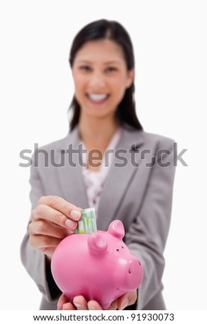 Money being put into piggy bank by smiling businesswoman against a white background - stock photo