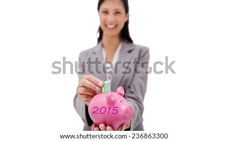 Money being put into piggy bank by smiling businesswoman against 2015 in grey