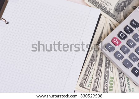 money, calculator and blank notebook with copy space - stock photo