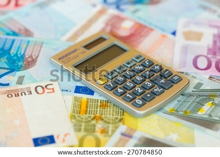 Money. Calculator and pencil over international currencies - stock photo