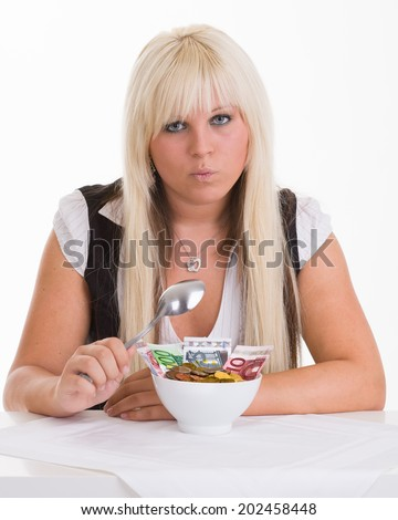 Money can not be eaten - woman with plate full of money - stock photo