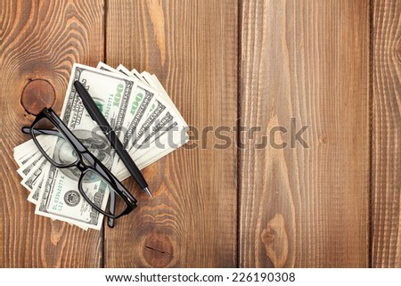 Money cash, glasses and pen on wooden table with copy space - stock photo