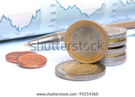 Money coins and ball pen in front of blue colored charts and statistics - stock photo