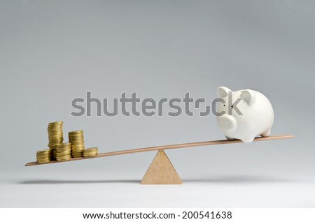 Money coins and piggy bank balancing on a seesaw - stock photo