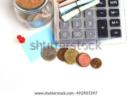 Money (coins) euros, calculator and some stationery on white, top view financial background concept.