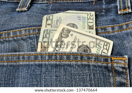 Money coming out of the back pocket of a pair of blue jeans - stock photo