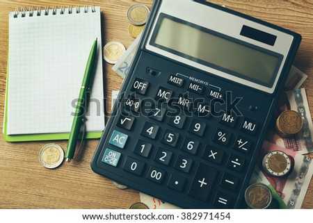 Money concept. Black calculator with banknotes and coins on wooden table, close up - stock photo